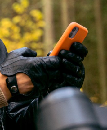 motorcyclist looking at smartphone in hand